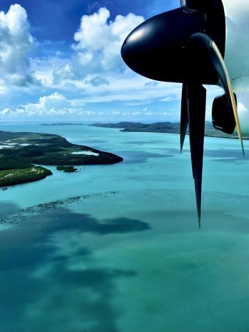 Aeroplane wing and view of crystal blue waters as the plan goes of the Torres Strait